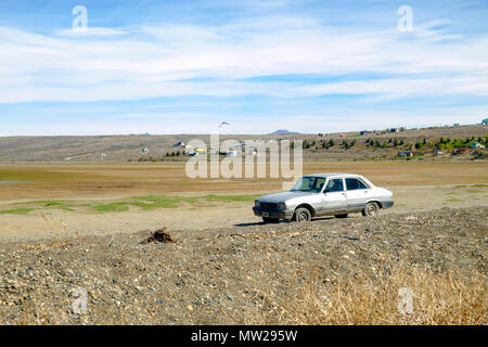 An isolated car is parked in El Calafate. The photo was taken during spring. In summer, Lake Argentino grows and floods this part of the city. - Stock Photo
