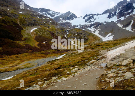 The hiking path towards the Martial Glacier near Ushuaia, Argentina, leads through patches of snow and next to a small stream towards a snowy glacier. - Stock Photo