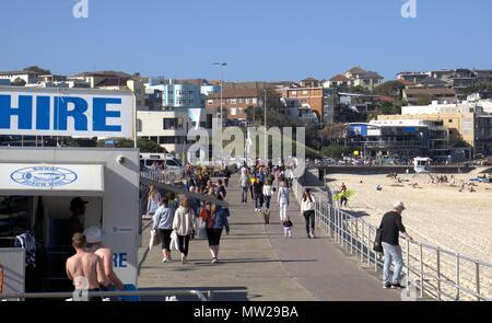 Hundreds of people walking at Bondi beach, Sydney Australia. People enjoying sunny day out at beach in Australia. Sydney people strolling at beach. - Stock Photo