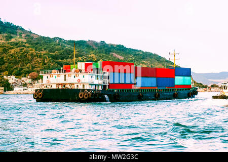 Large cargo nautical vessel in Victoria Harbor, Hong Kong at sunset. Business logistic, import, export concept. South China Sea, Pacific Ocean. - Stock Photo