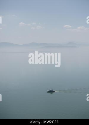 Fog over Lake Trasimeno on a peaceful morning, Umbria Trasimeno - Stock Photo