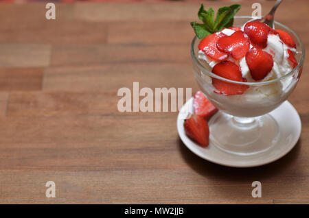 Vanilla ice cream with sliced strawberries and mint in a glass bowl on a white saucer. Standing on a wooden table - Stock Photo