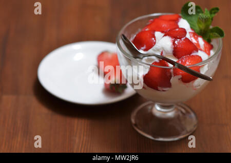 Vanilla ice cream with sliced strawberries and mint leaves in a glass bowl with a spoon. Next is a white saucer and halves of strawberries. Standing o - Stock Photo