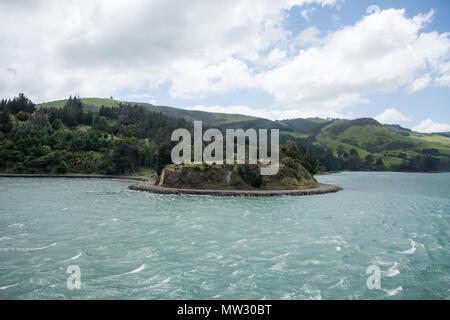 Stunning mountain landscape with coastal road under a cloudy sky in Dunedin, New Zealand - Stock Photo
