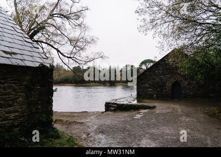 Scenic view of house in forest by lake against sky in Killarney a misty day - Stock Photo