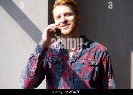 Portrait of attractive guy making phone call with solid background. Man with beard wearing flannel shirt talking on phone in sun coming from window. - Stock Photo