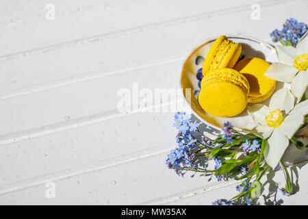 Macarons and flowers on a white background. Colorful french dessert with fresh flowers. Top view - Stock Photo