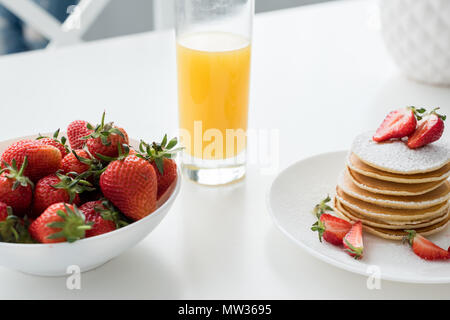 close-up shot of tasty pancakes with strawberries and orange juice - Stock Photo