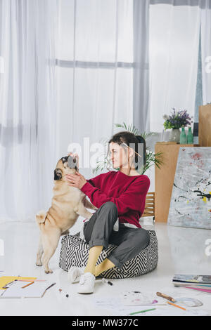 Pretty lady playing with pet dog on floor of home office - Stock Photo