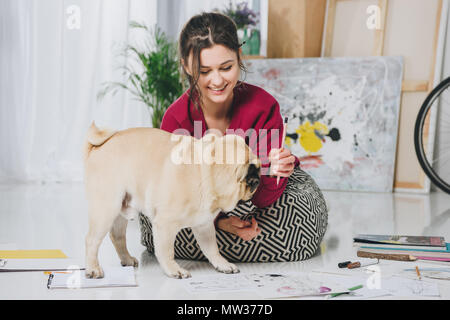 Pretty lady playing with pug puppy on floor - Stock Photo