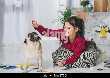 Young girl playing with pug on floor of modern home office - Stock Photo