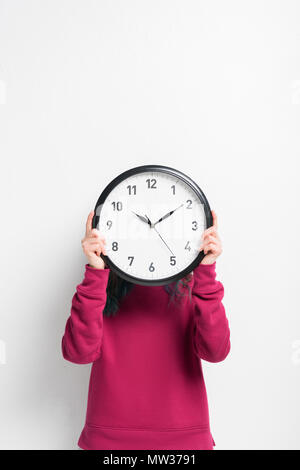 Girl holding clock over her face isolated on white - Stock Photo