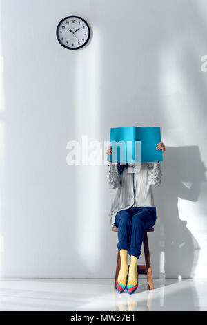 Attractive young girl reading and holding book over her face - Stock Photo