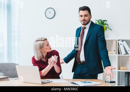 young businesswoman holding crumpled paper and looking at male colleague in office - Stock Photo