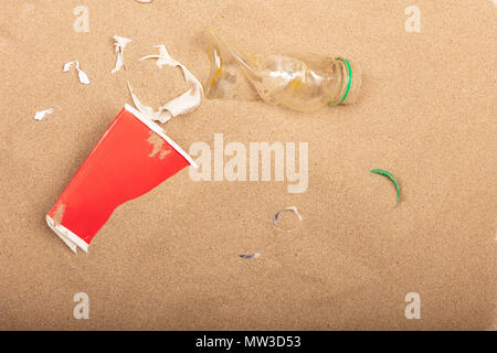 Waste plastic bottles and other types of wastes are lying on the sand of  a beach - Stock Photo