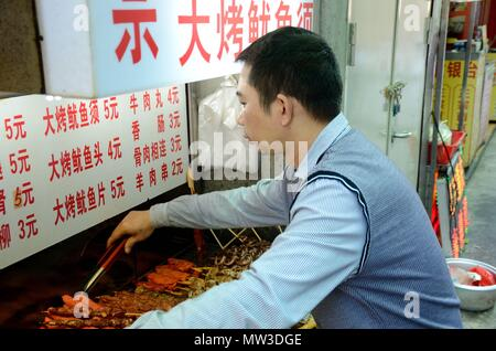 SHENZHEN, CHINA - APRIL 3: man offers spicy snacks made in deep-oil on April 3rd, 2018. - Stock Photo