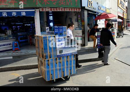 SHENZHEN, CHINA - APRIL 3: SEG famous electronic market in HuaQiangBei road. Man pushes cart with monitors on April 3rd, 2018. - Stock Photo
