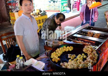 SHENZHEN, CHINA - APRIL 3: night market in Futian, man offering fried potato and dumplings on April 3rd, 2018. - Stock Photo