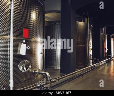 Large fermenters steel tanks stand in a row, wine modern factory equipment - Stock Photo