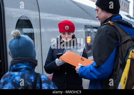 Saint Petersburg, Russia: a train conductor in a red beret of a Sapsan express train checks in a passenger with a child using electronic device. - Stock Photo