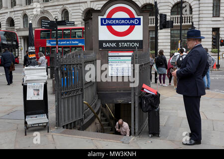 A businessman uses his mobile phone and another emerges from Bank Underground Station at the corner of King William Street in the City of London, on 30th May 2018, in London, England. - Stock Photo