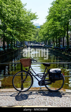 Bicycle on bridge above a canal in center of The Hague, Netherlands - Stock Photo