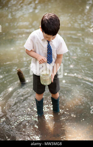 Catching Tadpoles in a Jam Jar. - Stock Photo
