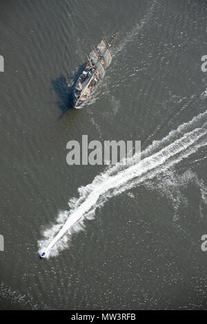 Aerial photo of tall ships leaving Liverpool on River Mersey with speedboat passing - Stock Photo