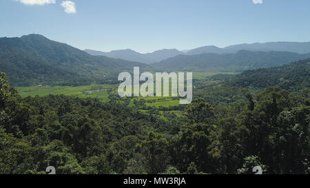 Mountain valley with village, farmland, rice fields. Aerial view of Mountains with green tropical rainforest, trees, jungle with blue sky. Philippines, Luzon. - Stock Photo