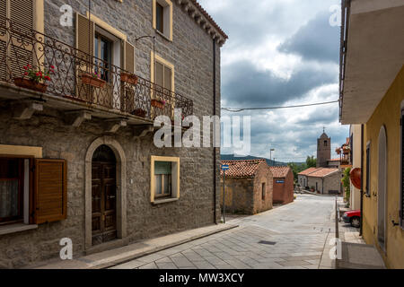A picturesque street in Sant'Antonio Di Gallura with view of the bell tower church, Sardinia - Stock Photo