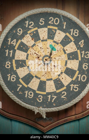 Close up old dartboard on old wood background. Top view. - Stock Photo