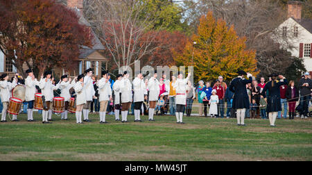 Colonial Williamsburg, Virginia Junior Fife and Drum Corps in formation and performing for a large tourist crowd as blue-coated senior officers salute - Stock Photo