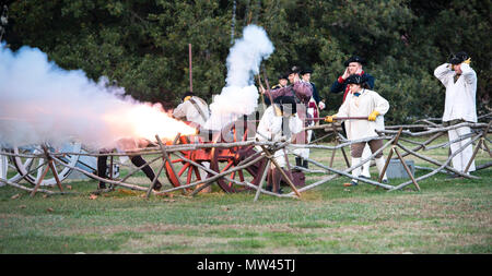 Firing of the cannon at day's end in historic Colonial Williamsburg. Captured in action, ears are covered and smoke streams out after the boom. - Stock Photo