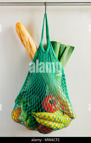 Green string shopping bag with vegetables, fruits and bread hanging on a hook in the kitchen - Stock Photo