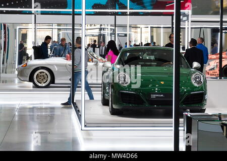 BERLIN, GERMANY - MAY 15 2018: People looking at Porsche sports cars standing at Volkswagen Group forum Drive on May 15, 2018 in Berlin, Germany. - Stock Photo