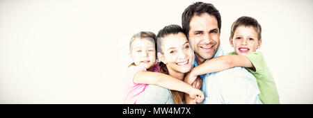 Portrait of smiling parents giving piggy-back to children - Stock Photo