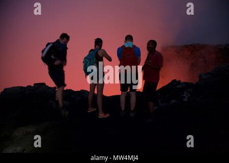 Tourists peer into the lava lake of Erta Ale volcano in the Danakil Depression - Stock Photo