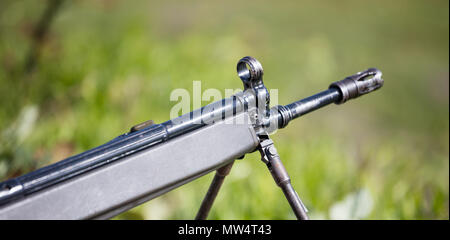 Firearm handgun on easel, stable for marking the target. Front side of weapon with close up view on blurred nature background. - Stock Photo