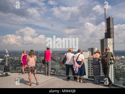 Visitors enjoying westerly views from the observation deck of the 56 storey Main Tower, Neue Mainzer Str, City of Frankfurt am Main, Hesse, Germany. - Stock Photo