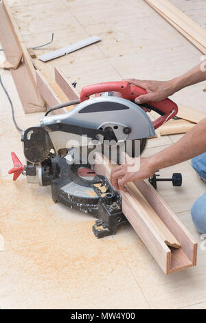 Carpenter using circular saw for wood - Stock Photo