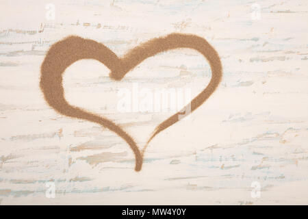 Decorative hearth shape of sea sand on a vintage blue and white painted wooden background with copy space - Stock Photo
