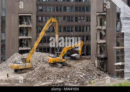 High view of demolition site with rubble, heavy machinery (excavators) working & demolishing empty office building - Hudson House, York, England, UK.