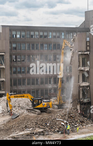 High view of demolition site with rubble, heavy machinery (excavators) working & demolishing empty office building - Hudson House  York, England, UK.