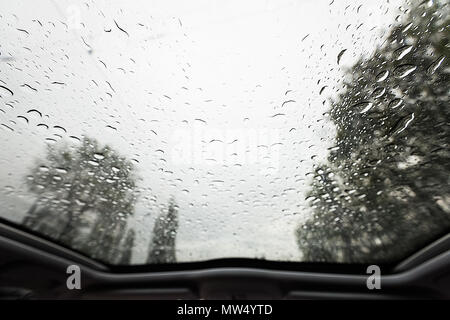 Look through windshield from inside the car at rainy weather - Stock Photo