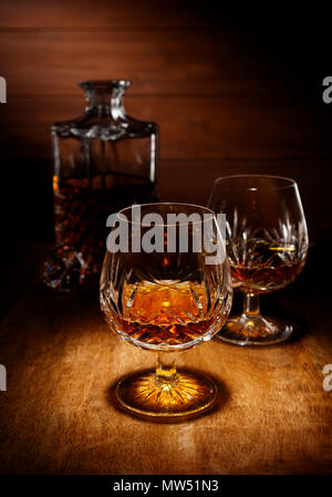 A spotlight on a crystal glass of brandy with a decanter in the backghround, shot on a wooden table top. - Stock Photo