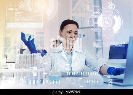 Professional scientist holding a flask while working on the laptop - Stock Photo