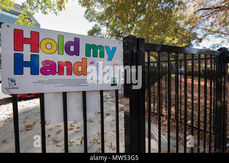 A Hold My Hand sign at a park exit in Ku-Ring-Gai on Sydney's north shore. This is a road safety initiative to protect children under 10 years of age. - Stock Photo