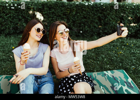 Portrait of two young women standing together eating ice cream and taking selfie photo on camera in summer street. - Stock Photo