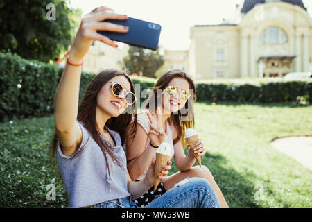 Two women friends take selfie while eating ice cream near river at sunset in summer - Stock Photo