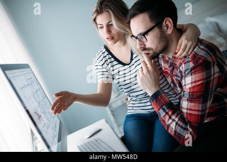 Young attractive designers working on project together - Stock Photo